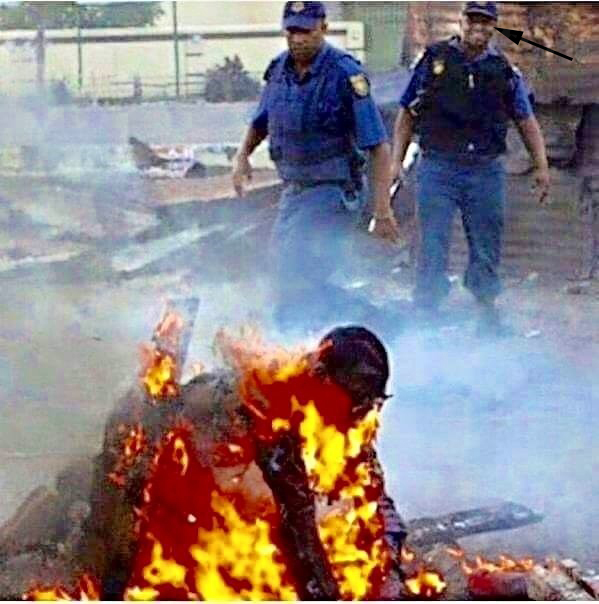 A picture taken in South Africa recently during the on-going clashes shows two South African policemen, with one of the law enforcers, see arrow, seemingly laughing at the burning victim. NET PHOTO