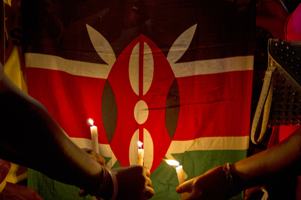 Makerere University students hold candles in front of a Kenyan flag on April 8, 2015 in commemoration of the 148 lives lost during a recent attack by the Al-Shabab insurgents in Garissa, Kenya. The Islamist terrorist group killed mostly students in the recent attacks in one of the biggest attacks in Kenya since 1998. PHOTO BY ISAAC KASAMANI