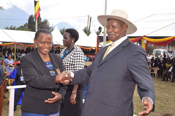 Museveni shakes hands with Lucy Nakyobe the state house financial Comptroller after receiving a medal of exemplary service.