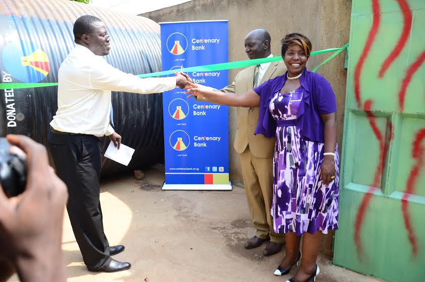 Patrick Odhiambo, the Centenary Bank Bwaise Branch Manager, cuts the tape with Mr and Mrs Serunjogi, the proprietors of Malaika Orphanage Children Foundation in Kawempe, last week