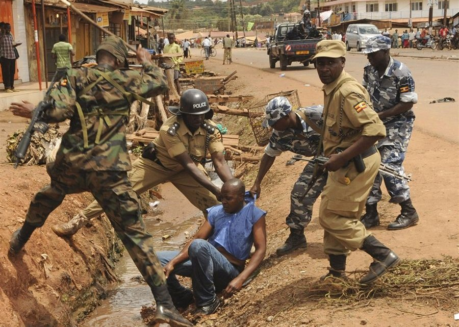 Uganda Police officers rough up a man who was participating in a protest