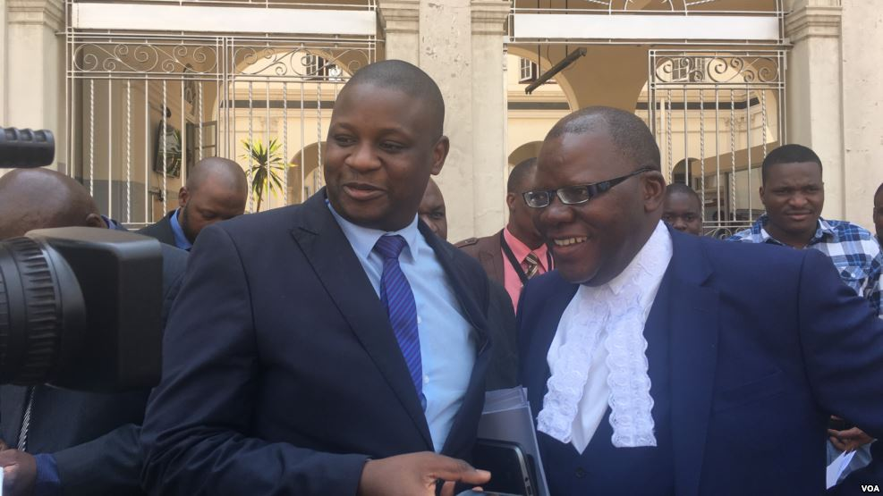 Tendai Biti, (R), opposition leader and member of Zimbabwe Lawyers for Human Rights, and Dzimbabwe Chibga from the rights group talk to reporters outside the High Court in Harare, Zimbabwe, September 2016. The two represented Zimbabwean opposition parties in court. (S. Mhofu/VOA).