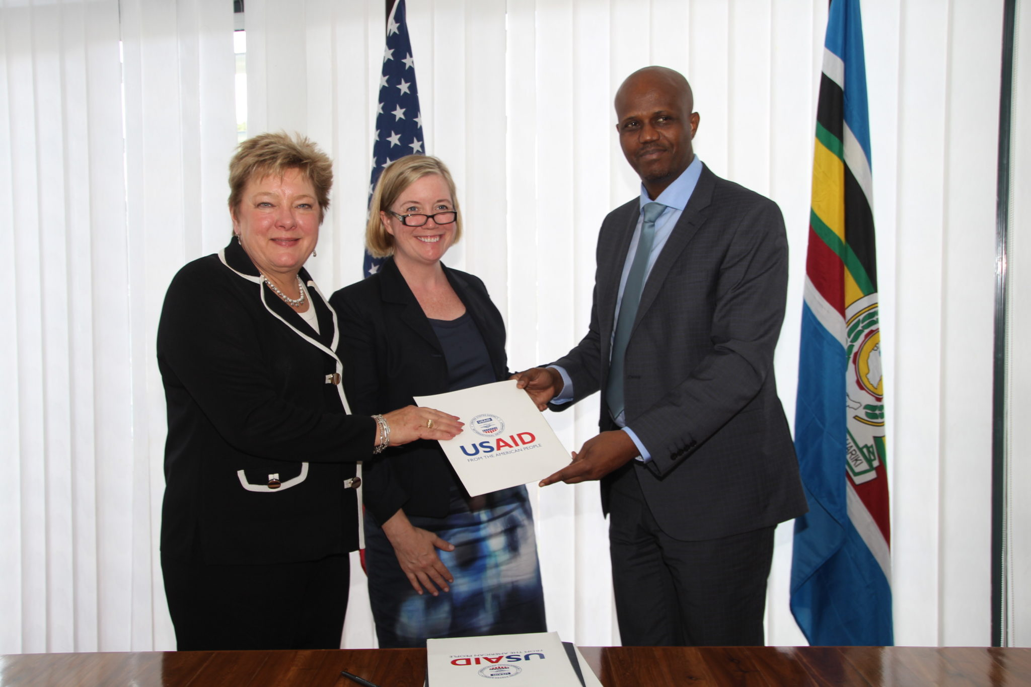 EAC Secretary General Amb. Liberat Mfumekeko exchanges signed copies of the five-year EAC-USAID Regional Development Objective Grant Agreement with Ms. Karen Freeman (USAID East Africa and the Chargé d'Affaires of the US Embassy in Tanzania, Ms. Virginia Blaser (centre).