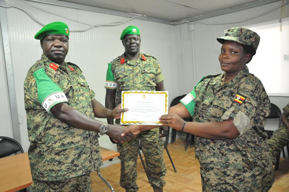 Lt. Col. Charles Monday, the specialist in Air defence and field Artillery rotating out with UGABAG XVII (right) receives certificate of recognition from the outgoing Uganda contingent commander Brig. Sam Okiding (left) as Outgoing UGABAG XVII commander (centre) looks on.